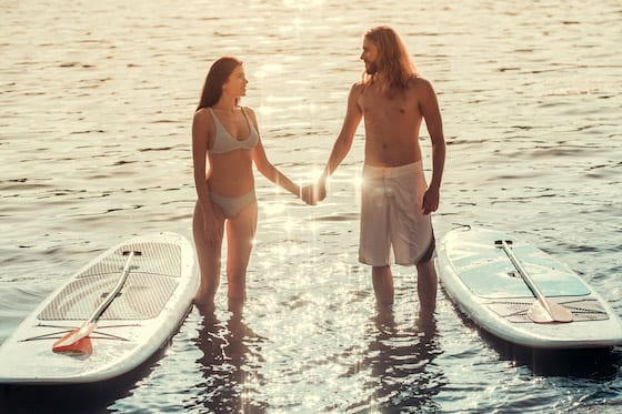 couple with paddleboards